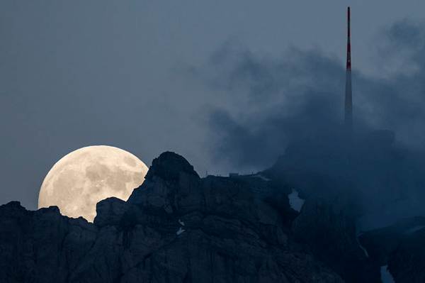 Supermoon Rising Above a Swiss Peak